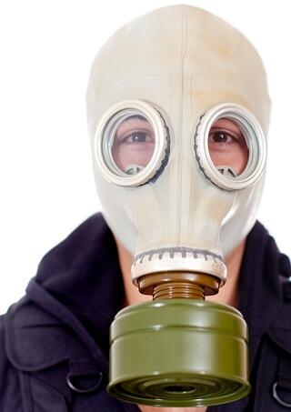 Man wearing a gas mask on his face - isolated over a white background.jpeg